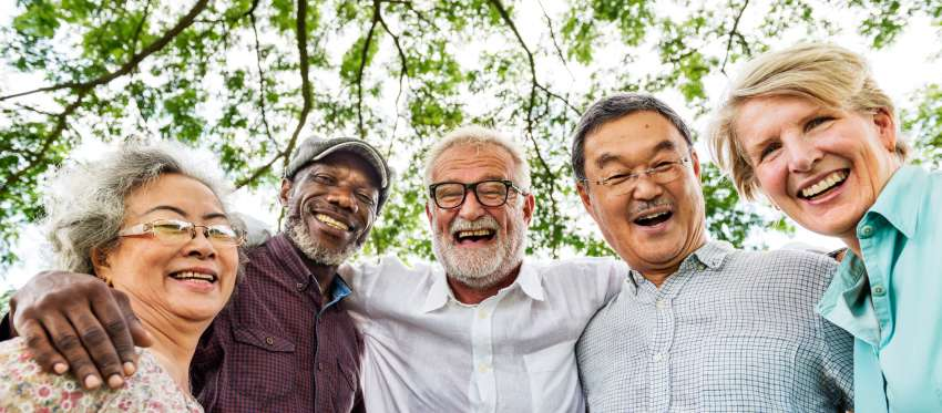 A smiling group of retirement-age people stand with their arms around one another's shoulders.